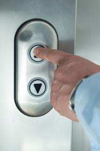 Image of elevator button being pressed